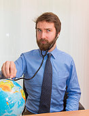 Doctor listening to the Earth with stethoscope.