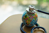 Global healthcare and save the world concept. Stethoscope on mini global ball.