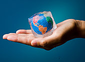 Conceptual image about saving Earth. The globe frozen into a melting icecube.