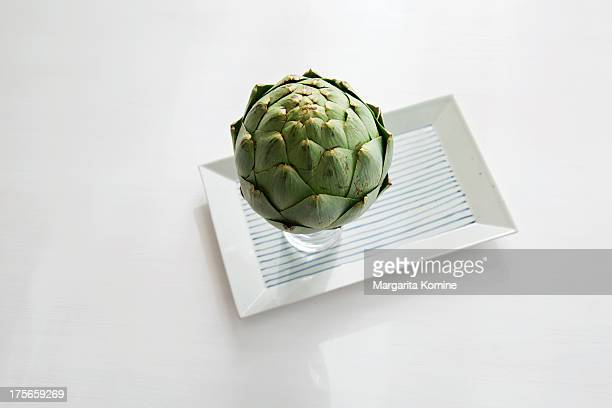 Globe artichoke in a vase on a plate