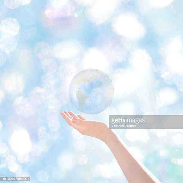 Globe floating over woman's hand