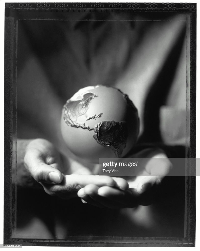 Globe hovering above cupped hands, close-up (B&W) : Stock Photo