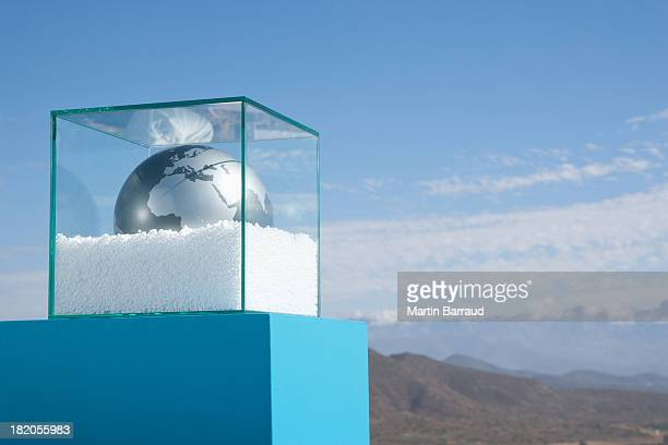 Globe in glass box on pedestal with gravel