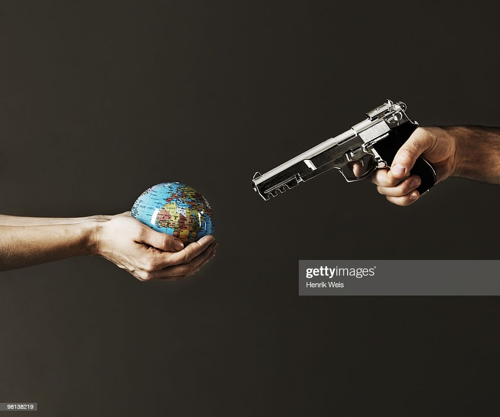 globe in hand with gun aimed at it : Stock Photo