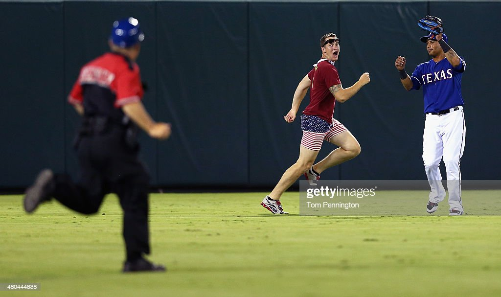 A Globe Life Park security officer chases a fan across the field as Leonys Martin #2 of the Texas Rangers looks on in the top of the eighth inning at Globe Life Park in Arlington on July 11, 2015 in Arlington, Texas.