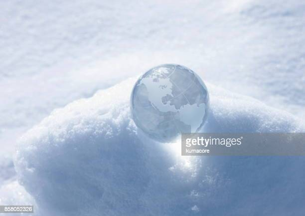 Globe made of glass on snow