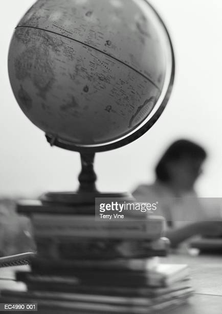 Globe on stack of books, woman reading in background (B&W)