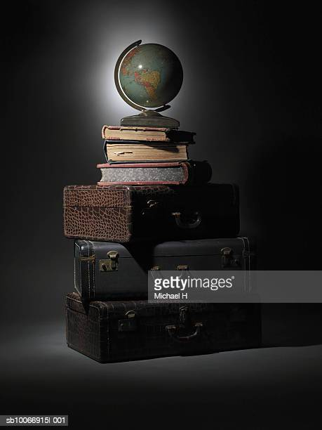 Globe on top of stack of old suitcases and books