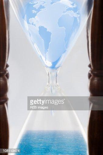 Globe squeezing through hour glass