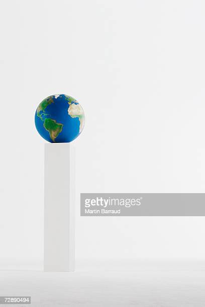 Globe standing on pedestal in empty white room, close-up