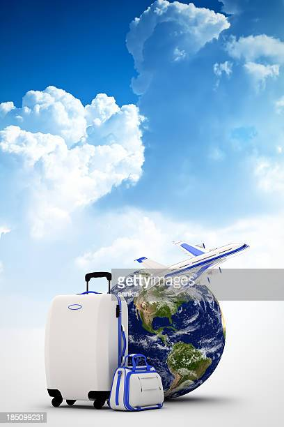 Globe, suitcases and plane on blue sky background