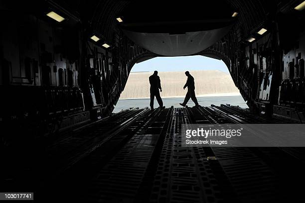 C-17A Globemaster III loadmasters go through prefight checks on the ramp.