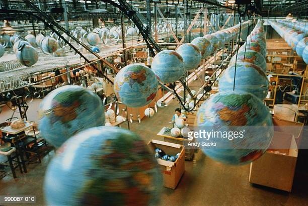 Globes high up on transport system above factory
