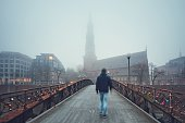 Man is walking on the iron bridge to the church in mysterious fog. Hamburg, Germany.