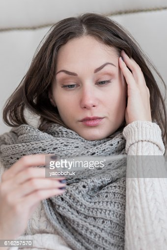 Gloomy ill woman having a high fever : Foto de stock