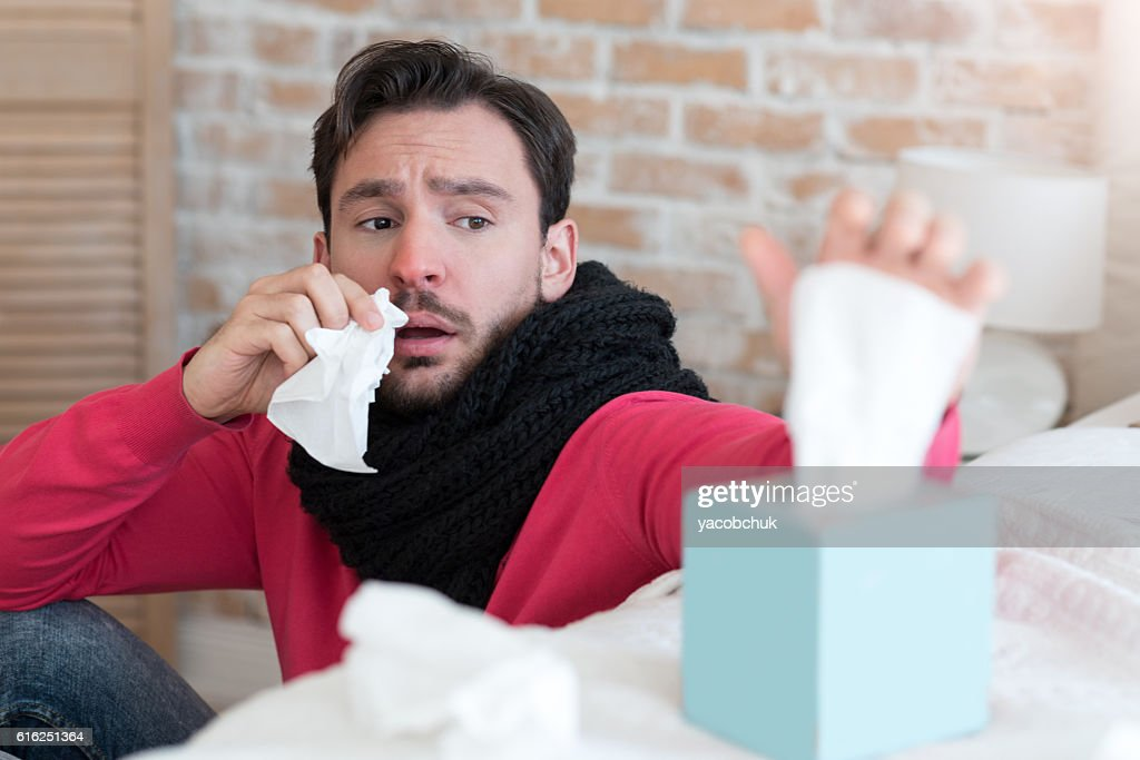 Gloomy tired man taking a tissue out of the box : Stock Photo