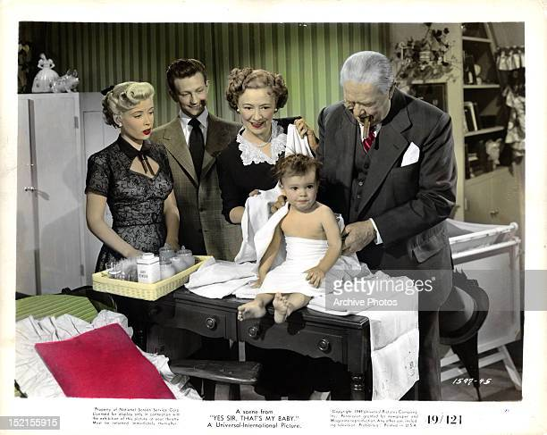 Gloria DeHaven Donald O'Connor a woman and Charles Coburn look at a baby in a scene from the film 'Yes Sir That's My Baby' 1949