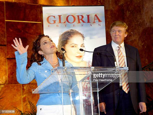 Gloria Estefan waves to fans as she announces her final tour 'Live and ReWrapped Summer 2004 Tour' during a news conference as Donald Trump looks on...
