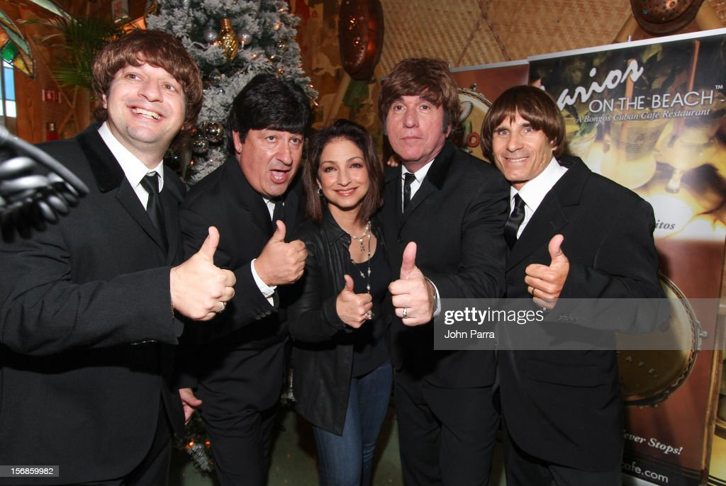 Gloria Estefan (C) with The Beatles inpersontors participate in 5th Annual Thanksgiving Feed A Friend at Bongos on November 22, 2012 in Miami, Florida.