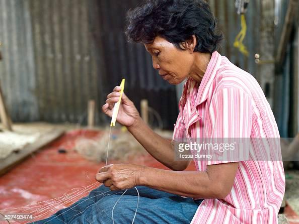 Gloria Mandawe repairs her husband's fishing nets Tamiao Bantayan Island The Philippines On November 6 2013 Typhoon Haiyan hit the Philippines and...