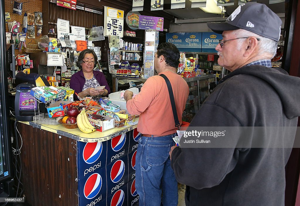 Gloria Yee (L) sells Powerball tickets at her corner store on May 17, 2013 in San Francisco, California. People are lining up to purchase $2 Powerball tickets as the multi-state jackpot hits $600 million.