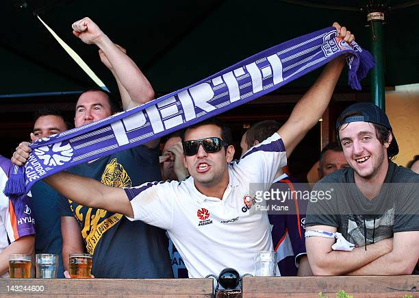 Glory fans look on from a balcony at the Elephant and Wheelbarrow pub as police attend to trouble makers on the street after the ALeague Grand Final...