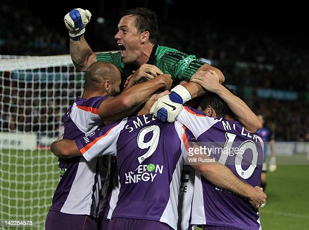 Glory goalkeeper Daniel Vukovic jumps on Shane Smeltz after he scored the team's third goal during the ALeague Elimination Fimal match between the...