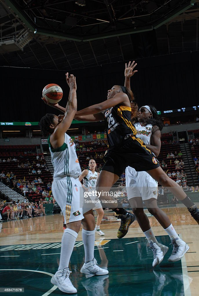 Glory Johnson #25 of the Tulsa Shock shoots against Tanisha Wright #30 and Crystal Langhorne #1 of the Seattle Storm during the game on August 10,2014 at Key Arena in Seattle, Washington.