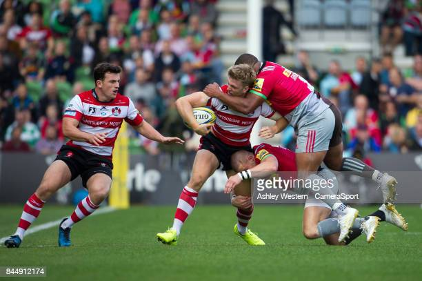 Gloucester Rugby's Ollie Thorley offloads to Matt Scott as he is tackled by Harlequins' Kyle Sinckler and Mike Brown during the Aviva Premiership...