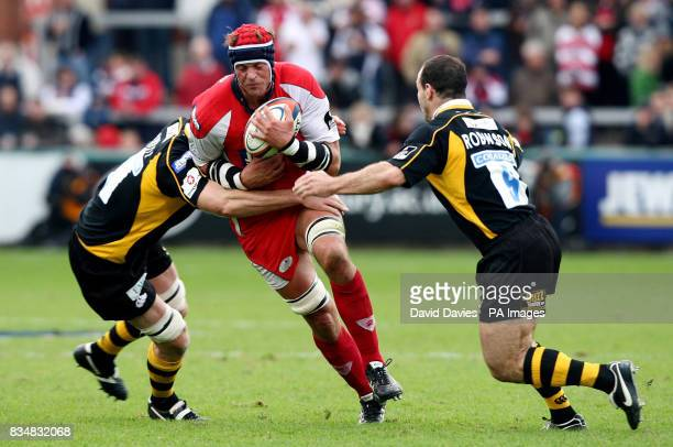 Gloucester's Alex Brown is tackled by Wasps Richard Birkett and Mark Robinson during the EDF Energy Cup match at Kingsholm Stadium Gloucester