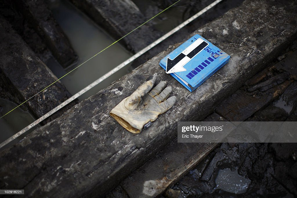 A glove and a book sit on remnants of what is thought to be an 18th century ship at the site Ground Zero Construction Site in July 15, 2010 New York City. The wood hulled vessel is approximately 30 feet long and was found 20 to 30 feet below street level on Tuesday morning.
