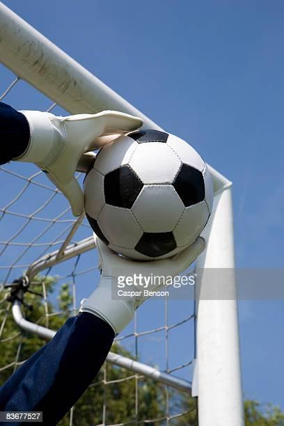 Gloved goalie's hands catching a soccer ball