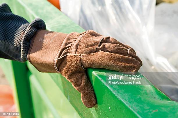 Gloved hand holding onto edge of dumpster
