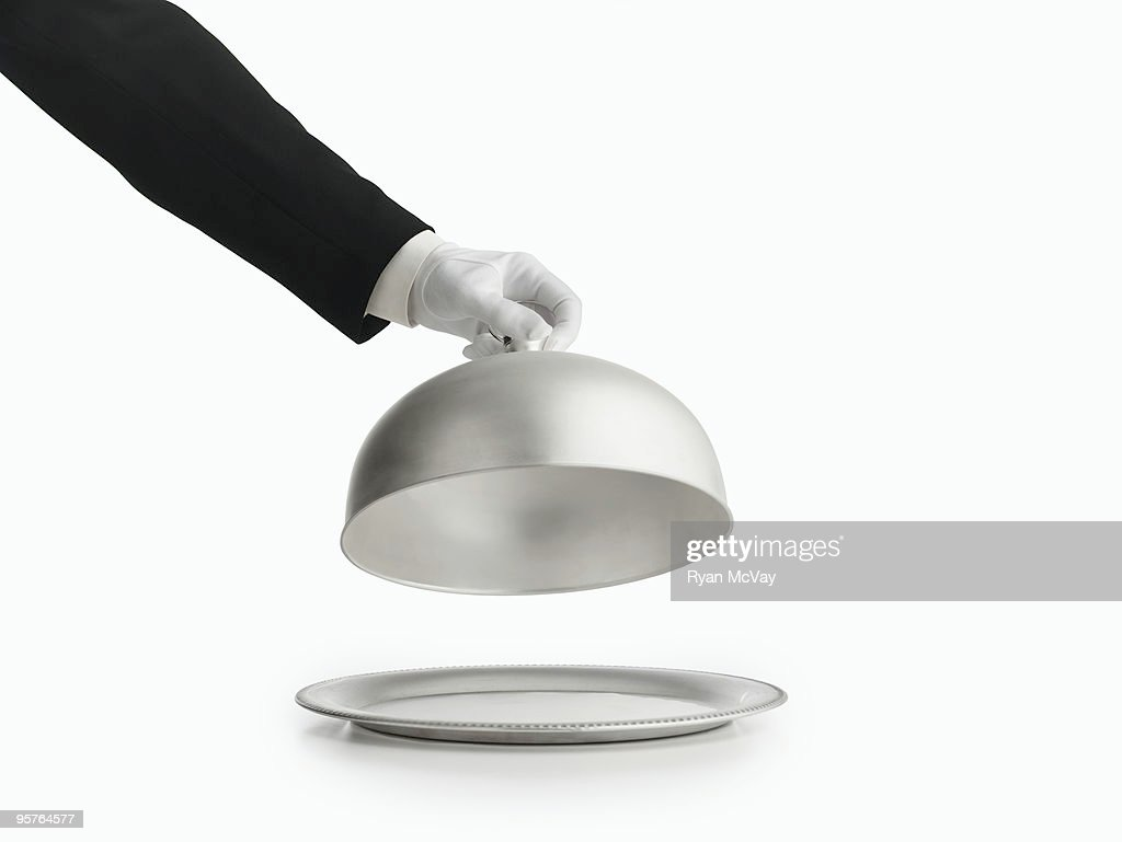 gloved hand lifting silver lid off a platter : Stock Photo