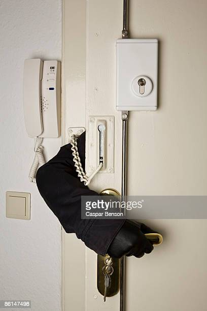 A gloved hand reaching inside a locked door