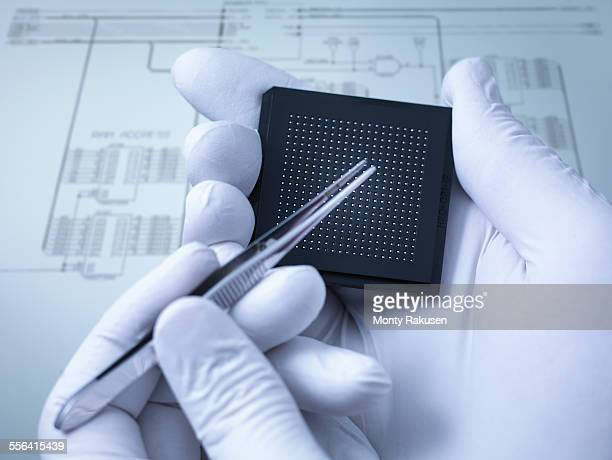 Gloved hands holding small electronic chips in laboratory, close up