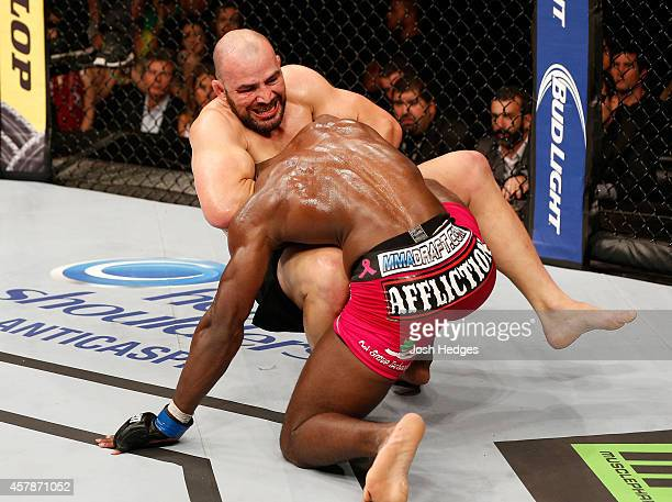 Glover Teixeira of Brazil attempts to secure a guillotine choke submission against Phil Davis in their light heavyweight bout during the UFC 179...