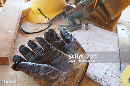 Gloves, blueprints, and tool belt on table