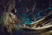Blue coloured glow worms in a cave in New Zealand, lit up by flashes. A stream runs through the middle.