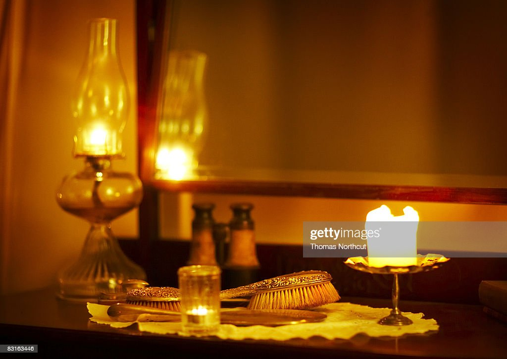 Glowing candles on top of vanity  with antiques : Stock Photo