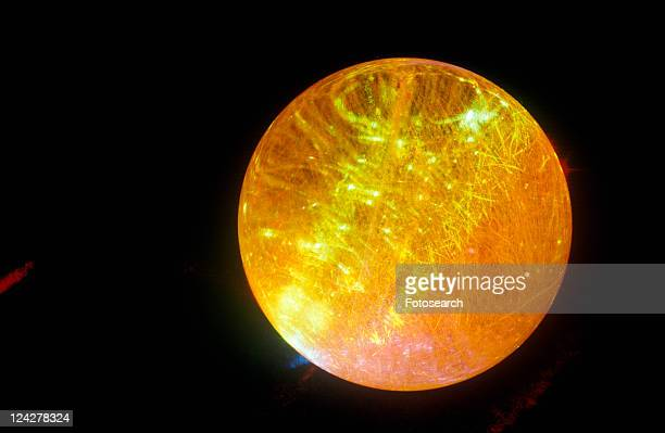 A glowing crystal sphere as orange laser light shines through