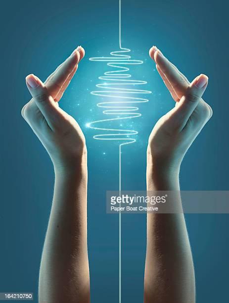 A glowing digital light wave in between hands
