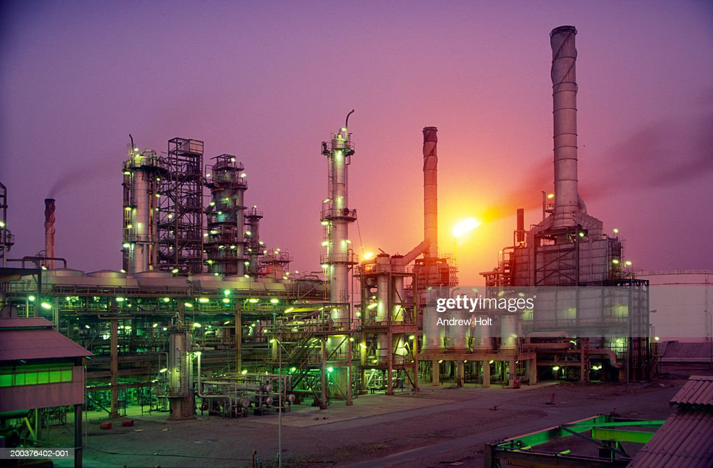 Glowing flame of flare stack burning waste gas at oil refinery, dusk : Stock Photo