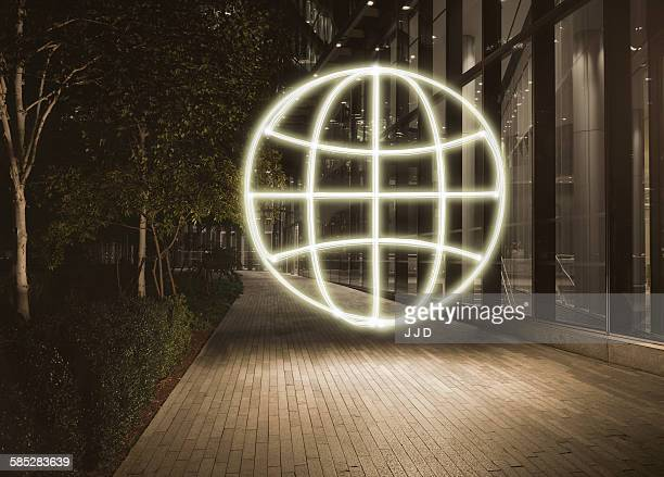 Glowing globe symbol in city at night