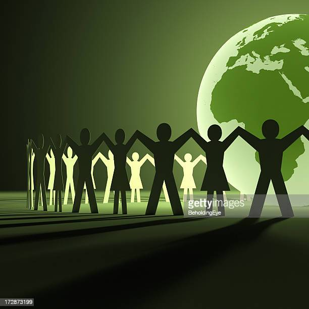 Glowing green globe with paper cutouts of men and women