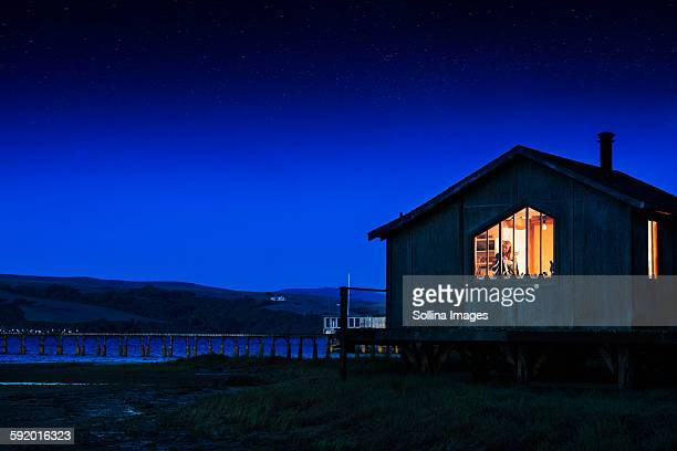 Glowing house and dock over remote lake
