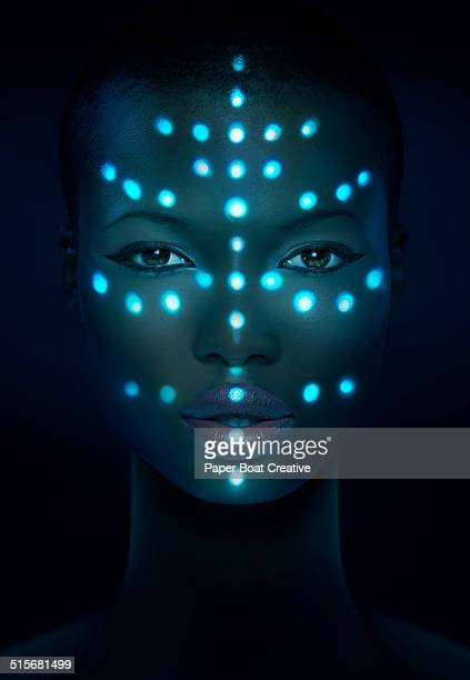 Glowing laser beam dots on a woman's face
