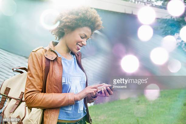 Glowing lights and young woman using smartphone