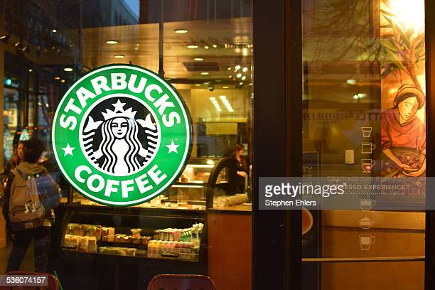 A glowing Starbucks Coffee sign hangs in the window of a store in downtown Seattle Washington where the company is headquartered Customers and...