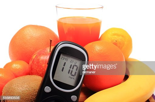 Glucometer, fresh natural fruits and glass of juice : Stockfoto